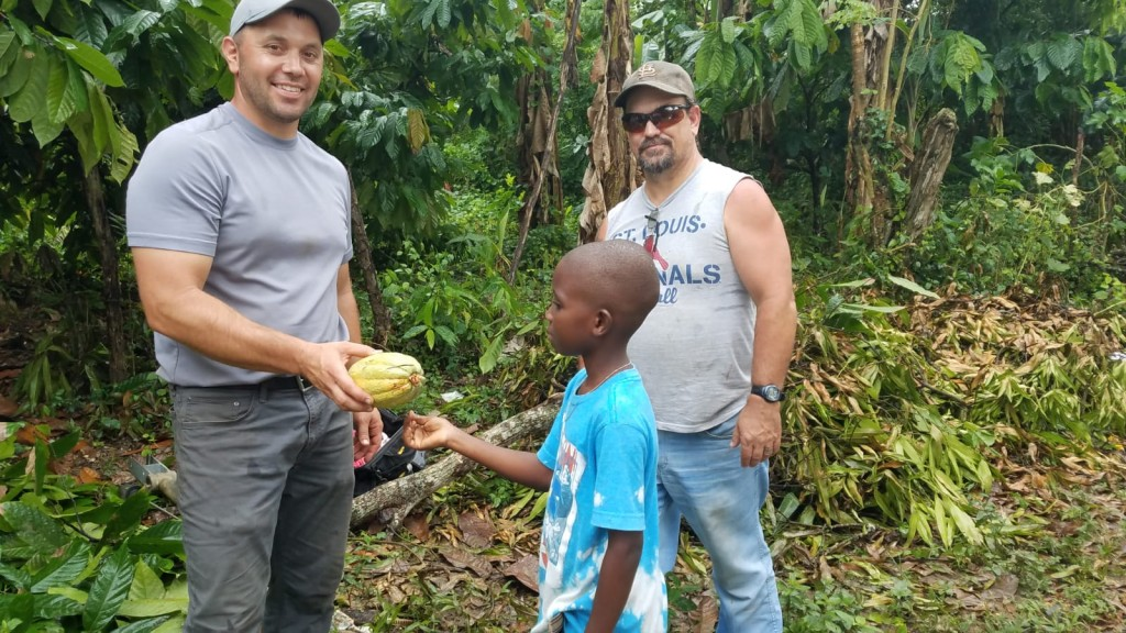 Cristian, one of the village boys,  giving Matt a pod of cocoa beans as a thank you gift.